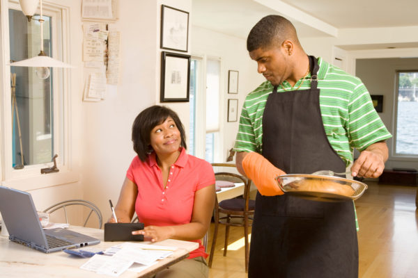 man cooking dinner while woman fills out a check while budgeting