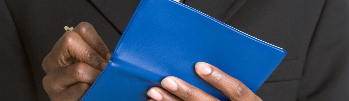 man's hands holding checkbook